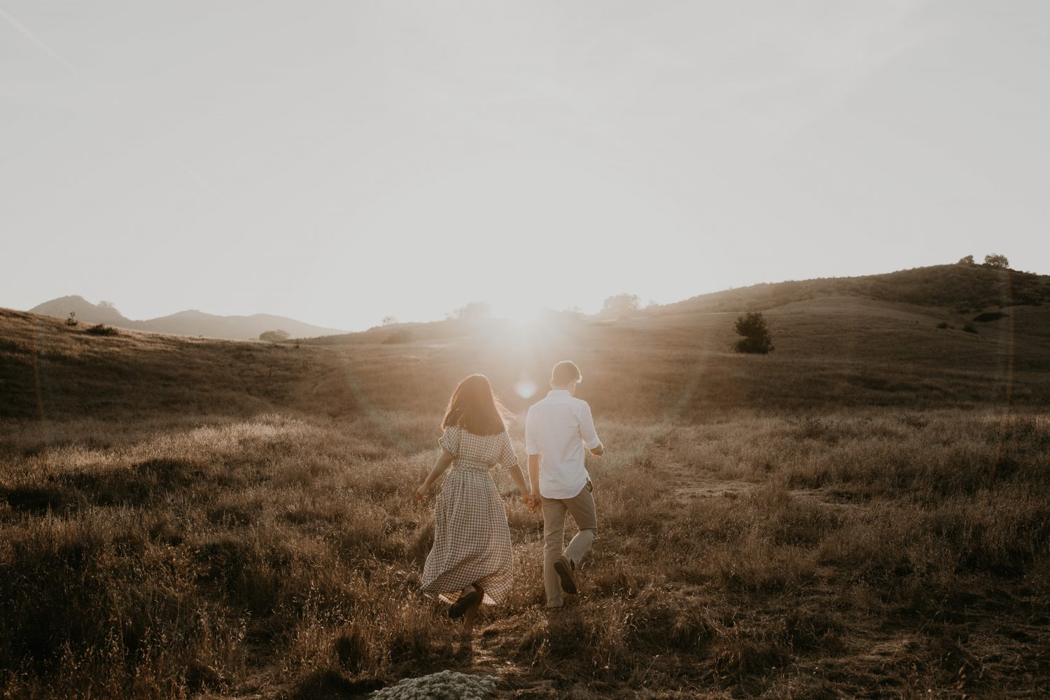 Couple walking into the sunset in a big empty field of yellow grass, image by Fatima Elreda Photo
